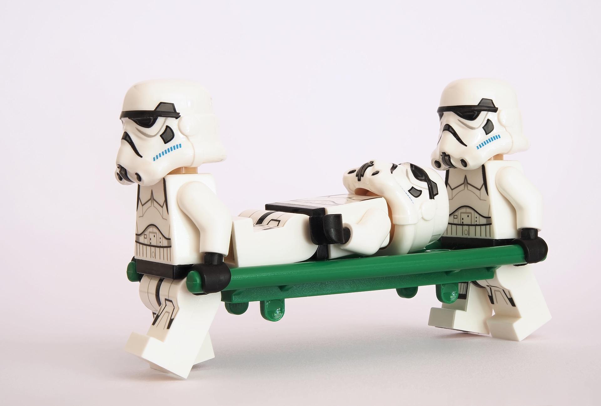 Deux stormtroopers en portent un troisième sur un brancard.